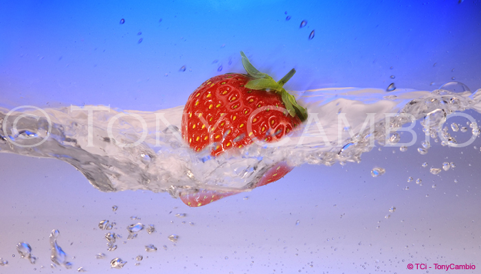 A Strawberry splashing into water, partially submerged